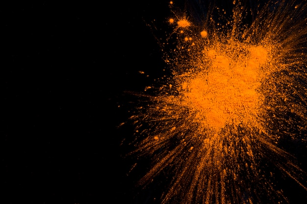 Orange powder explosion on black background