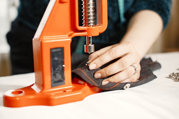 Orange press for clothes. buttons on fabric. woman with sewing tools
