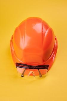 明るい黄色のオレンジ色の保護用ヘルメットとその近くの保護メガネ。垂直方向。保護作業服と建設業界のコンセプト