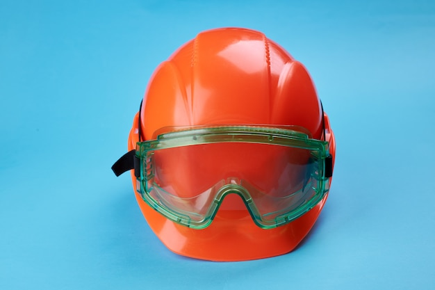 Orange protective helmet and safety glasses near it on a bright blue. protective workwear and construction industry concept