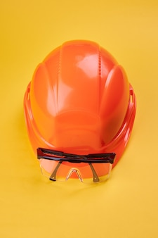 Orange protective helmet and safety glasses near it on a bright yellow. vertical orientation. protective workwear and construction industry concept