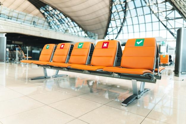 空港のオレンジ色の公共座席は空港ターミナル内に間隔を置いて配置されています