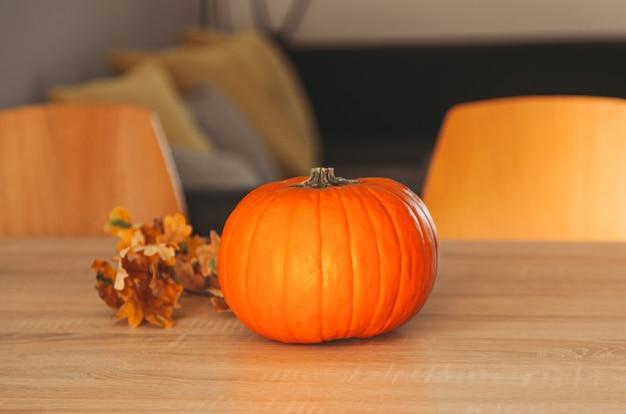 部屋のテーブルにオレンジ色のカボチャと紅葉。こんにちは秋、居心地の良いゆっくりとした生活。幸せな感謝祭。