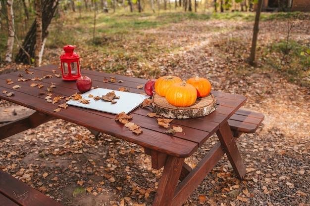 オレンジ色のカボチャとテーブルの上のラップトップコンピューターの近くに残します。秋の季節の時間