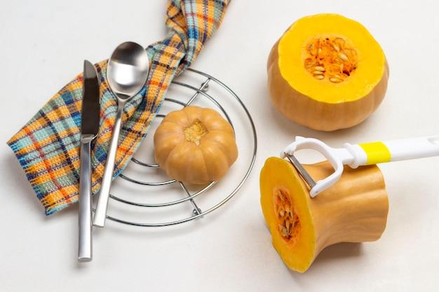 オレンジ色のカボチャと皮むき器。ナプキンにナイフとスプーン。金属製のスタンドにカボチャのかけら。白色の背景。上面図。