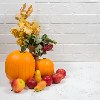 Orange pumpkin, apples, pears, autumn yellow leaves and rowan berries on a white table against a brick wall background.