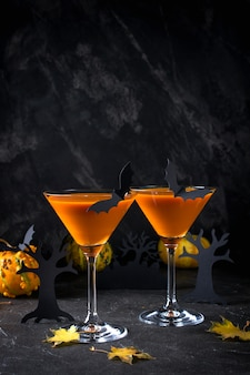 オレンジ色のカボチャ、パーティーや休日の装飾のコピースペースと黒の背景上のハロウィーンの飲み物