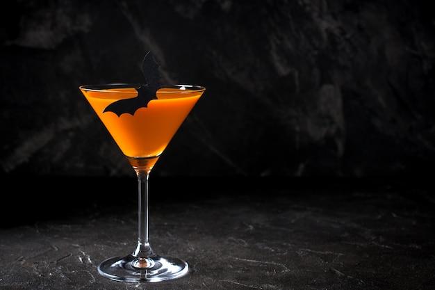 コピースペースと黒の背景上のパーティーのためのオレンジ色のカボチャマティーニハロウィーンドリンク