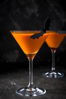 Оранжевый тыквенный мартини на хэллоуин для вечеринки на черном фоне с копией пространства