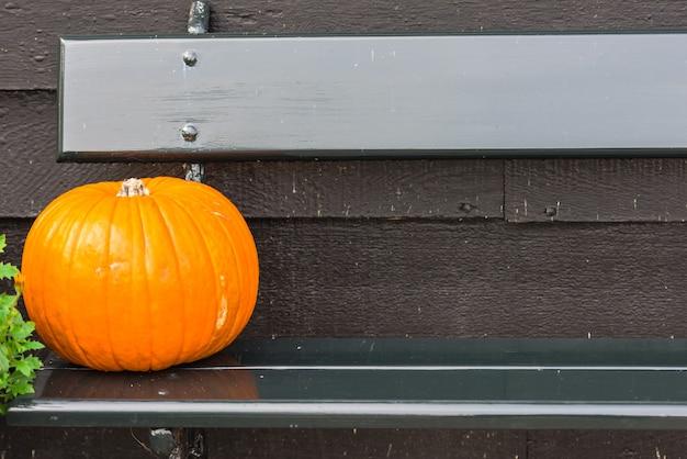 Оранжевая тыква на деревянной скамейке. снято с выборочной фокусировкой