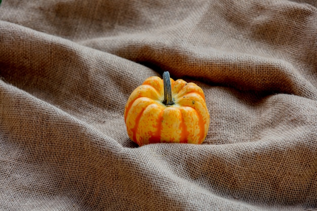 Orange pumpkin on rumpled sackcloth.