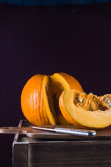 Orange pumpkin with chopping board and knife on wooden table