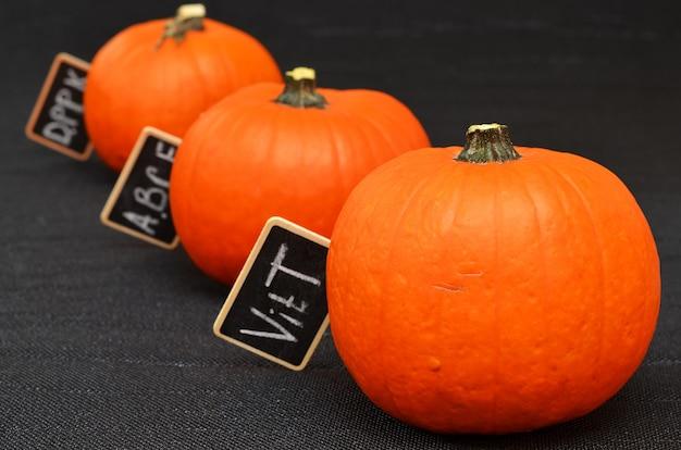 Оранжевые тыквы и таблетки с обозначением витаминов, содержащихся в плодах тыквы.