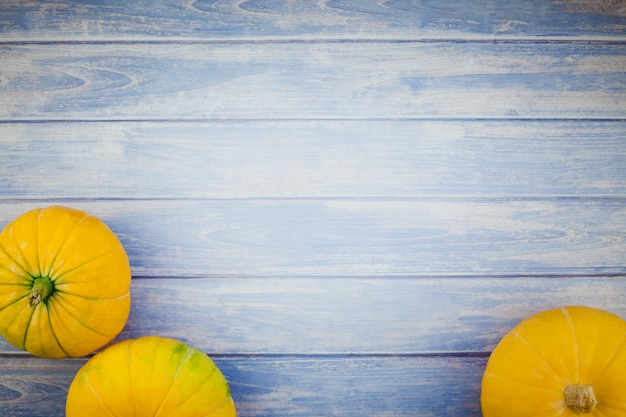 Orange pumpkins on blue wooden background