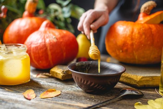 木製のテーブルの背景に蜂蜜とシナモンで焼くためのオレンジ色のカボチャ