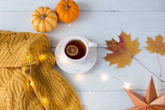Orange pumpkins, knitted orange sweater, autumn leaves, a cup of tea with lemon