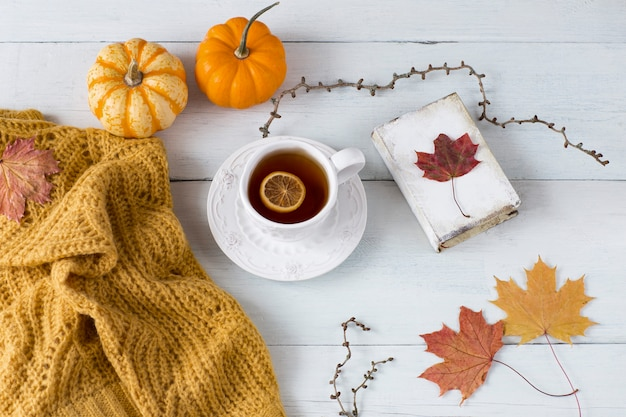 Orange pumpkins, knitted orange sweater, book, autumn leaves, a cup of tea with lemon on a white wooden table