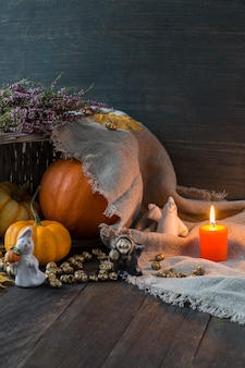 Orange pumpkins, orange candle, autumn leaves and ghost figures and witches