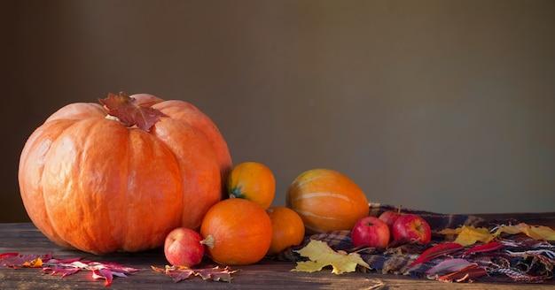 Оранжевые тыквы с осенними листьями на деревянном столе
