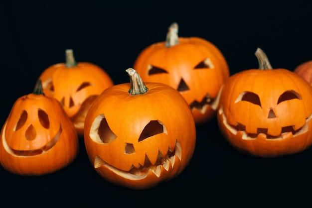 Orange pumpkins with carved faces for halloween celebration