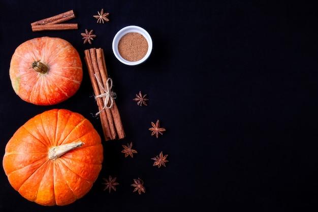 Orange pumpkins with cinnamon sticks and anise stars on black