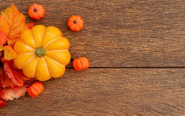 カエデの葉とオレンジ色のカボチャは、ハロウィーンの茶色のレトロな木製の卓上背景に横たわっていた