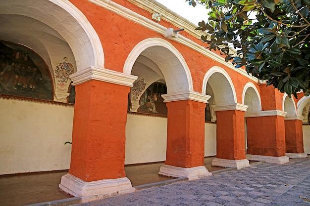 Orange red columns and wall fresco paintings in monastery of santa catalina arequipa peru