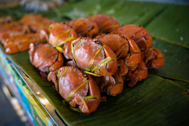 Orange red steamed crabs placed on table in a green banana leaf in thai restaurant