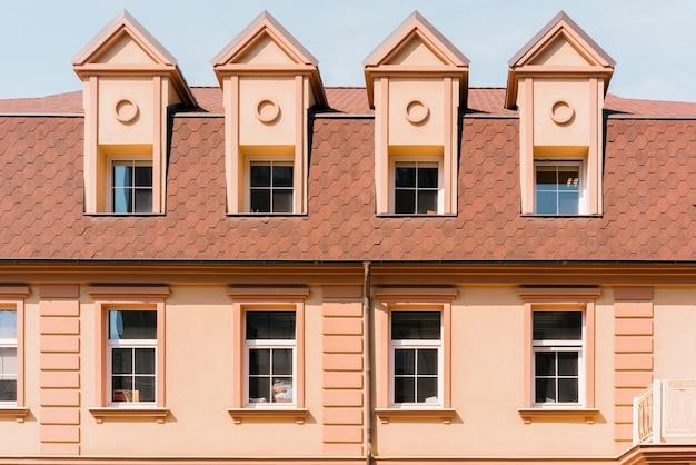 オレンジ色に改装された建物で、屋上に4つのドーマー窓があります。ドーマーウィンドウ。復元されました。リノベーション