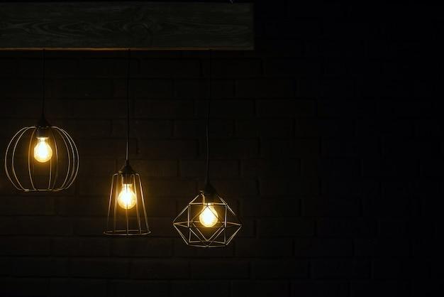 어두운 검은 벽돌 벽의 배경에 나무 보드에 매달려 오렌지 복고풍 램프. 광고 또는 텍스트에 대 한 장소를 가진 현대 템플릿. 가벼운 교수형 인테리어 디자인
