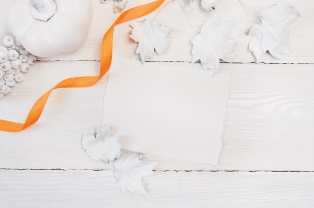 Orange ribbon, white pumpkin, berries and leaves