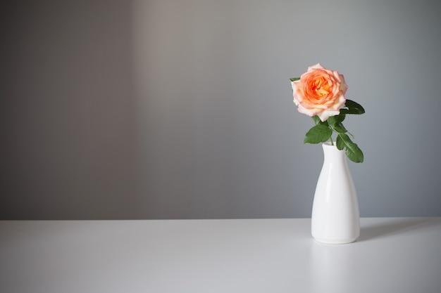 Оранжевая роза в белой вазе на сером фоне