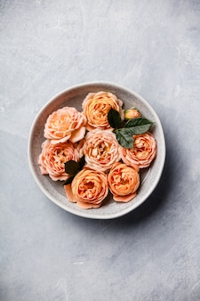 Orange roses floating in water on concrete