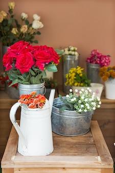 Оранжевые розы в серебряном лейке на деревянном столе