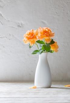 표면 흰 벽에 꽃병에 오렌지 장미
