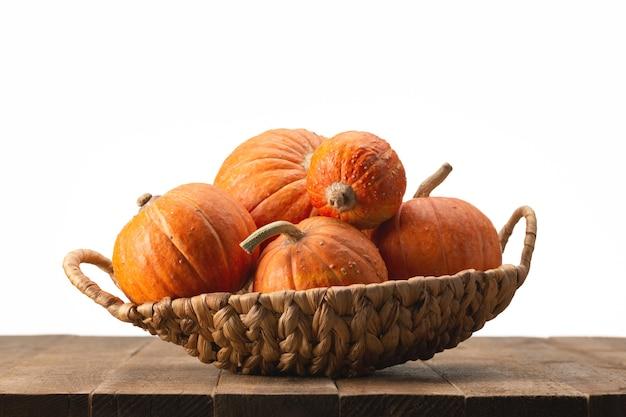 木製のテーブルの籐のバスケットにオレンジ色の丸いカボチャ。ハロウィンデザイン。
