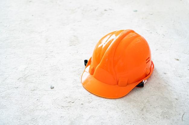 Conrete 배경에 오렌지 안전 안전모입니다. 아이디어를 구축하고 구성합니다.