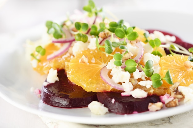 Orange salad with baked beetroot goat cheese microgreens and nuts