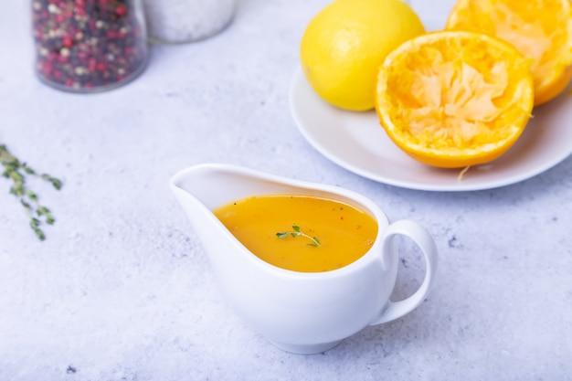 Апельсиновый соус для утки (птицы) в белом соуснике. крупным планом, селективный фокус.