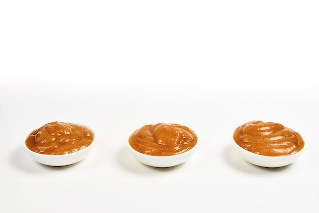 白い背景の上の白いプレートのオレンジソース。