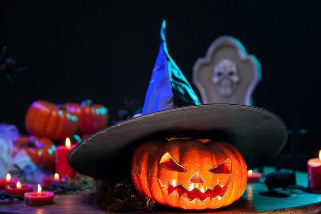 Оранжевая страшная тыква на хэллоуин в черной шляпе ведьмы. украшение хэллоуина на деревянном столе.