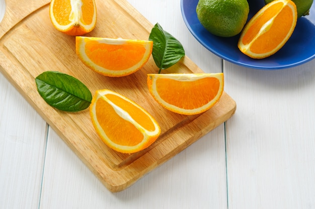 Orange segments with leaves on white wooden surface