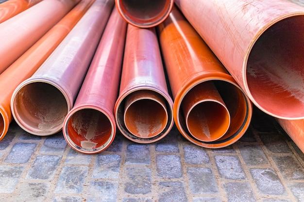 Оранжевые канализационные трубы лежат на строительной площадке. подготовка к земляным работам для прокладки подземного трубопровода.