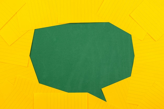 Orange sheets of paper lie on a green school board and form a chat bubble with copy space for text.