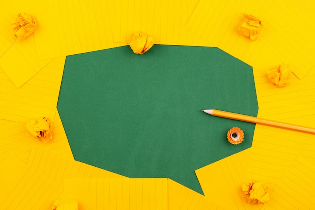 Orange sheets of paper lie on a green school board and form a chat bubble with pencil, crumpled papers and copy space for text.