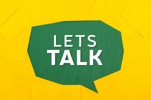 Orange sheets of paper lie on a green school board and form a chat bubble with text let's talk
