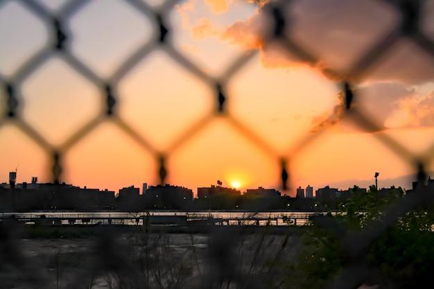 Orange sky in new york city panorama with skyscrapers in manhattan skyline defocused fance