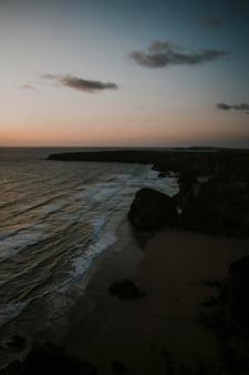 우울한 바위 해변 위로 오렌지 하늘