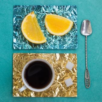 나무 표면에 노란색과 청록색 호일로 만든 스탠드에 오렌지 슬라이스와 커피 한 잔