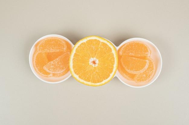 Долька апельсина и желейные конфеты на белой тарелке